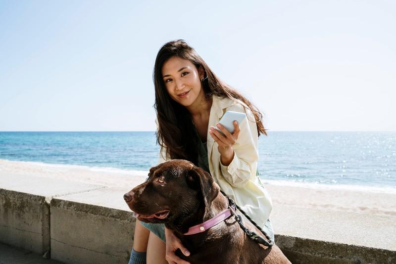 Dieses Bild zeigt eine Frau, die eine App nehmen ihrem Hund benutzt.