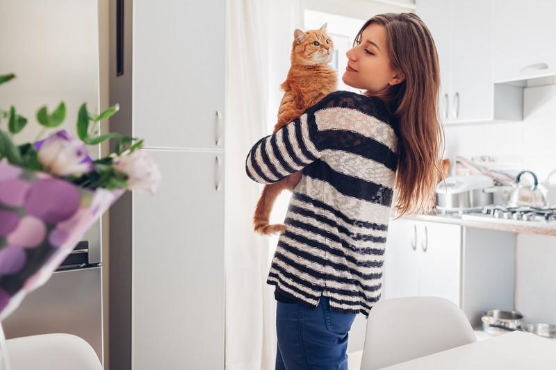 Frau hält ihre Katze auf dem Arm