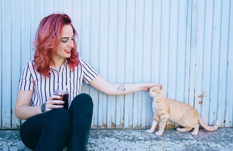 Katzensprache: Die Katze begrüßt mit Köpfchegeben freudig eine Frau