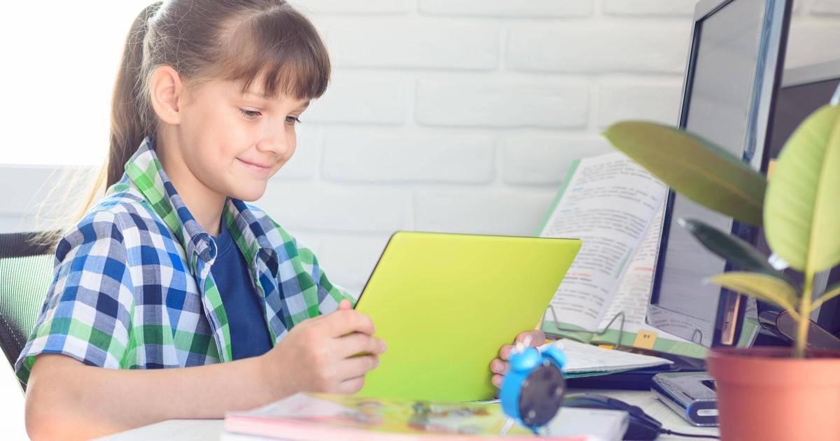 Kleines Mädchen hält eine Computerpräsentation, um Katze zu bekommen