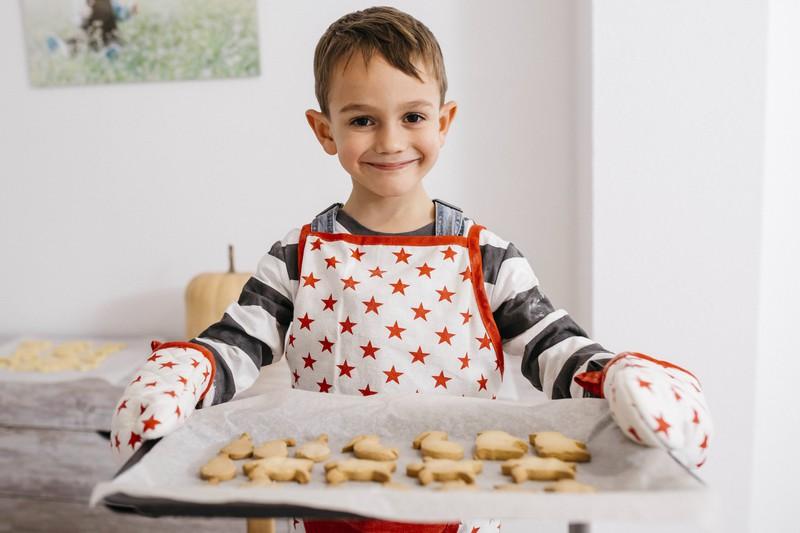 Ein Junge mit einem Blech Kekse